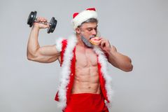 Holidays and celebrations, New year, Christmas, sports, bodybuilding, healthy lifestyle - Muscular handsome sexy Santa. Claus enjoys fresh baked piping hot Royalty Free Stock Photo