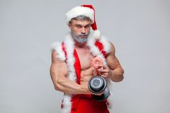 Holidays and celebrations, New year, Christmas, sports, bodybuilding, healthy lifestyle - Muscular handsome sexy Santa. Claus enjoys fresh baked piping hot Royalty Free Stock Photography