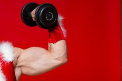 Holidays and celebrations, New year, Christmas, sports, bodybuilding, healthy lifestyle - Muscular handsome sexy Santa. Claus. on red background Stock Photo