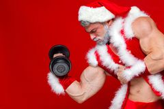 Holidays and celebrations, New year, Christmas, sports, bodybuilding, healthy lifestyle - Muscular handsome sexy Santa. Claus. on red background Royalty Free Stock Photo