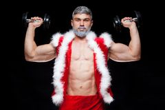 Holidays and celebrations, New year, Christmas, sports, bodybuilding, healthy lifestyle - Muscular handsome sexy Santa. Claus. on a black background with Stock Photos
