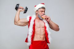 Holidays and celebrations, New year, Christmas, sports, bodybuilding, healthy lifestyle - Muscular handsome sexy Santa. Claus enjoys fresh baked piping hot Stock Photography