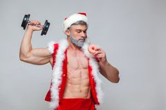 Holidays and celebrations, New year, Christmas, sports, bodybuilding, healthy lifestyle - Muscular handsome sexy Santa. Claus enjoys fresh baked piping hot Stock Images