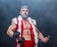 Holidays and celebrations, New year, Christmas, sports, bodybuilding, healthy lifestyle - Muscular handsome sexy Santa Stock Images