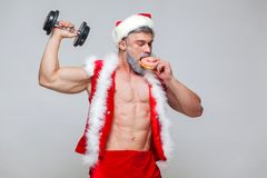 Holidays and celebrations, New year, Christmas, sports, bodybuilding, healthy lifestyle - Muscular handsome sexy Santa. Claus enjoys fresh baked piping hot Royalty Free Stock Photos