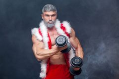 Holidays and celebrations, New year, Christmas, sports, bodybuilding, healthy lifestyle - Muscular handsome sexy Santa. Claus. on a black background with Stock Image