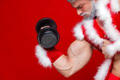 Holidays and celebrations, New year, Christmas, sports, bodybuilding, healthy lifestyle - Muscular handsome sexy Santa. Claus.Isolated on red background Stock Photos