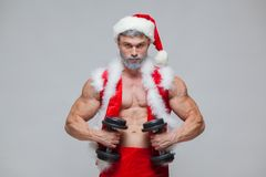 Holidays and celebrations, New year, Christmas, sports, bodybuilding, healthy lifestyle - Muscular handsome sexy Santa Stock Image