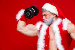 Holidays and celebrations, New year, Christmas, sports, bodybuilding, healthy lifestyle - Muscular handsome sexy Santa. Claus. on red background Royalty Free Stock Images