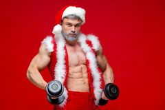 Holidays and celebrations, New year, Christmas, sports, bodybuilding, healthy lifestyle - Muscular handsome sexy Santa Stock Photo