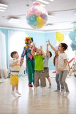 Holidays, childhood and celebration concept - several kids having fun and jumping on birthday party in entertainment stock photo