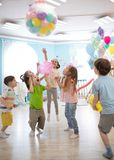 Holidays, childhood and celebration concept - several kids having fun and jumping on birthday party in entertainment. Holidays, childhood and celebration concept royalty free stock images