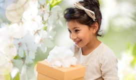 Happy girl with gift box over cherry blossom. Holidays, childhood and people concept - happy girl with birthday gift box over cherry blossom background Royalty Free Stock Images