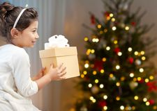 Happy little girl with christmas gift at home royalty free stock photo