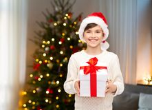 Happy boy in santa hat with gift box on christmas royalty free stock images