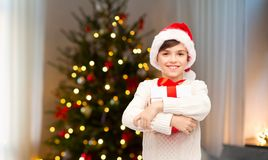 Happy boy in santa hat with gift box on christmas royalty free stock image