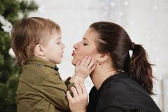 Holidays, christmas, love and happy family. Little boy kissing mother Stock Images