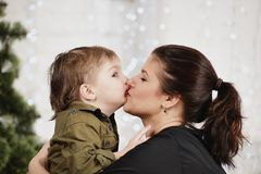 Holidays, christmas, love and happy family. Little boy kissing mother Royalty Free Stock Image
