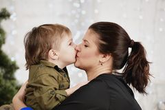 Holidays, christmas, love and happy family. Little boy kissing mother Stock Photo