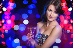 Holidays, christmas, people celebration concept. Closeup of woman in evening dress with glass over holidays lights bokeh background Stock Photography