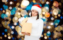 Displeased woman in santa hat with christmas gift Royalty Free Stock Images