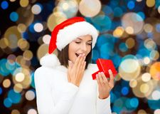 Happy woman in santa hat opening christmas gift Stock Photos