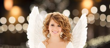 Happy woman with angel wings over christmas lights. Holidays, christmas and people concept - happy young woman or teenage girl with angel wings over lights Royalty Free Stock Images
