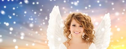 Teenage girl with angel wings over snow. Holidays, christmas and people concept - happy young woman or teenage girl with angel wings over snow background royalty free stock photo