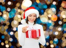 Smiling woman in santa hat with christmas gift Royalty Free Stock Images
