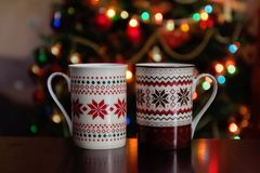 Holidays, christmas, winter, food and drinks concept - close up. Of candy canes and cups on wooden table over lights stock images