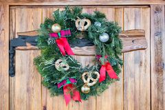Christmas wreath with pretzels, red bows and gold ornaments hanging on the wooden door. Holidays. Christmas wreath with pretzels, red bows and gold ornaments Stock Photography