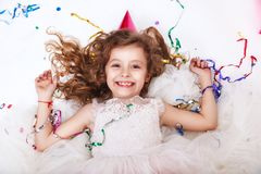 Holidays concept. Little funny girl lying in multicolored confetti on birthday party. Funny happy girl celebrating birthday party, smiling and lying in stock photos