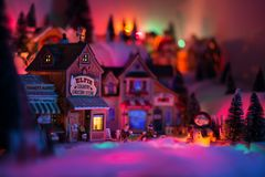 Holidays concept of miniature scenery in Christmas times. Christmas times in fairy tale town of elf miniature figurines with happy snowman standing while other royalty free stock photo
