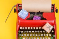 Holidays concept - typewriter with blank craft paper, gift boxes on yellow background. Holidays concept - red typewriter with blank craft paper, gift boxes on royalty free stock images