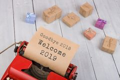 Red typewriter with text `Goodbye 2018 Welcome 2019`, gift boxes. Holidays concept - red typewriter with text `Goodbye 2018 Welcome 2019`, gift boxes on white stock images