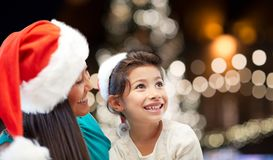 Mother and daughter in santa hats at christmas Stock Images