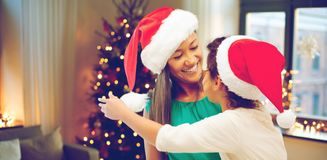Happy mother and daughter on christmas. Holidays and family concept - happy mother and daughter in santa hats over room with christmas tree background stock image