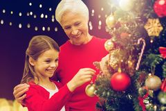 Happy family decorating christmas tree. Holidays, family and people concept - happy grandmother and granddaughter decorating christmas tree over lights Royalty Free Stock Images