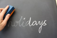 Holidays finished. The word holidays being rubbed off a blackboard, symbolic for returning to school (or work Royalty Free Stock Images