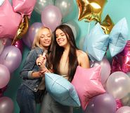 Holidays, friends   and people concept -  two women in casual we. Ar with microphone singing karaoke over  background of colorful ballons Royalty Free Stock Image
