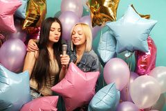 Holidays, friends   and people concept -  two women in casual we. Ar with microphone singing karaoke over  background of colorful ballons Stock Photography