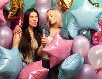 Holidays, friends   and people concept -  two women in casual we. Ar with microphone singing karaoke over  background of colorful ballons Stock Photo