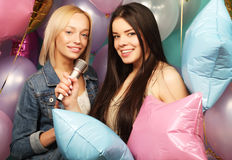 Holidays, friends   and people concept -  two women in casual we. Ar with microphone singing karaoke over  background of colorful ballons Royalty Free Stock Images