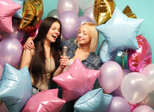 Holidays, friends   and people concept -  two women in casual we. Ar with microphone singing karaoke over  background of colorful ballons Stock Images
