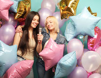 Holidays, friends   and people concept -  two women in casual we. Ar with microphone singing karaoke over  background of colorful ballons Stock Image