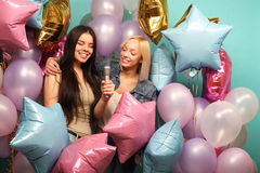 Holidays, friends   and people concept -  two women in casual we. Ar with microphone singing karaoke over  background of colorful ballons Royalty Free Stock Photo