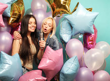 Holidays, friends   and people concept -  two women in casual we. Ar with microphone singing karaoke over  background of colorful ballons Royalty Free Stock Photos