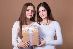 Holidays and friendship concept - girls with gift box over beige. Holidays and friendship concept - two girls with gift box over beige background Stock Photo