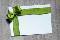 Holidays gift card with green bow. On wooden background Royalty Free Stock Images