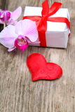Holidays gift, orchid and red heart Stock Photography